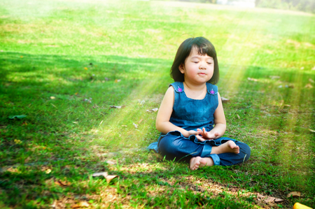 sunny morning: Little asian girl practicing mindfulness meditation outdoor in a park.