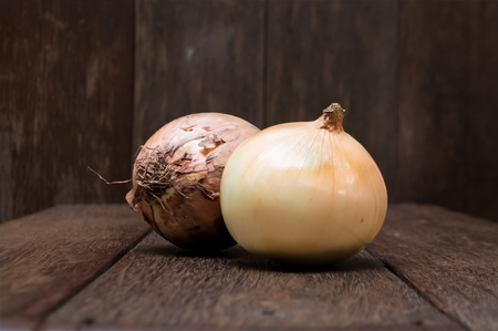 Peeled and unpeeled onions on vintage wood table. The onion is a vegetable most widely cultivated species of the genus Allium. Bulbs from the onion family have been used as food source for millennia.
