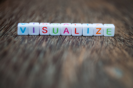 narrow depth of field: visualize word arranged from character cubes on wood table top. closeup. narrow depth of field.