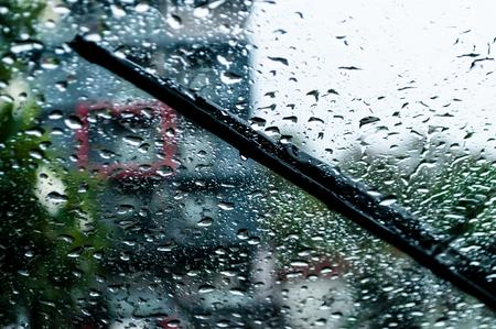 regendruppels en wisser op de voorruit van de auto. gebruik ruitenwissers en rijd voor de veiligheid langzaam in de regen. Stockfoto