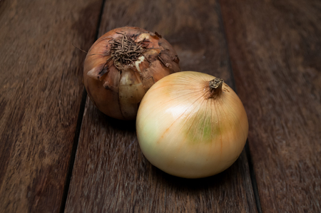 millennia: Peeled and unpeeled onions on vintage wood table. The onion is a vegetable most widely cultivated species of the genus Allium. Bulbs from the onion family have been used as food source for millennia.