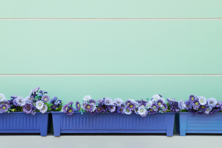 Blue rectangular plastic flowerpod with light violet, blue and white artificial flowers made of cloth fabric put on white cement wall sill against turquoise cement wall with white horizontal lines
