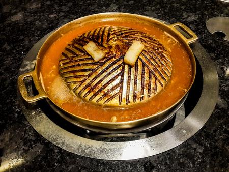 Parrilla de latón sucia, grasienta, usada, sartén frita con carne quemada pegajosa de color marrón oscuro y dos trozos de grasa de cerdo parcialmente quemada. Comida chatarra. Alto contenido de grasa, calorías y posibilidades de oxidante.