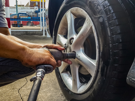 asian man hands holding pneumatic wrench screwing wet car tire for replacement after fixing air leak at garage.