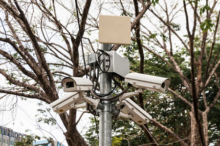 Four CCTV surveillance security cameras point in different directions in a park for public safety. Stock Photo