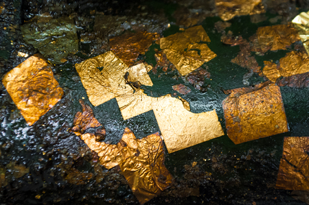 close-up shot on gold leaf gilded on dark oily surface of buddha statue Stock Photo