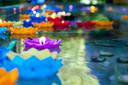 Lotus shape candle lit and float on water as sacred offering found in several religions and parts of the world. May be offering to gods, respect person, ancestor or nature spirits depending on belief.