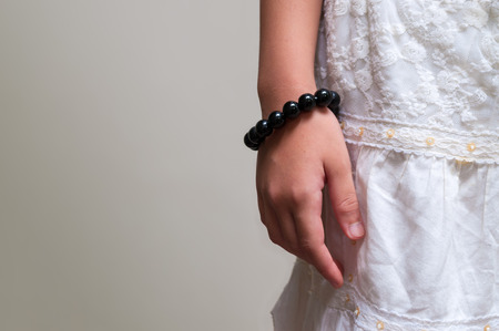 Black beads bracelet on girl hand. Can be used as fashion accessories, also as praying beads, for counting prayers or practicing mindfulness meditation. Some believe black stone has protection power. Stock Photo