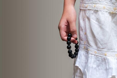 inconspicuous: Black beads bracelet in girl hand. Can be used as fashion accessories, also as praying beads, for counting prayers or practicing mindfulness meditation. Some believe black stone has protection power.