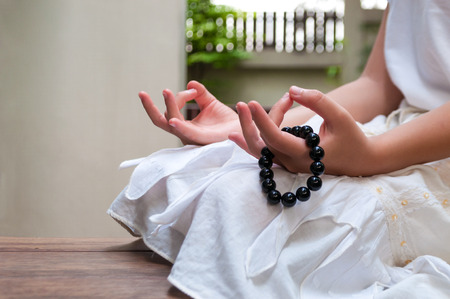 Black beads bracelet in girl hand. Can be used as fashion accessories, also as praying beads, for counting prayers or practicing mindfulness meditation. Some believe black stone has protection power.