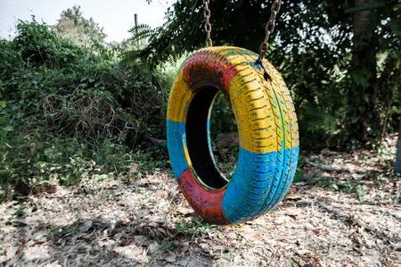 Swing made of painted old tire in government established children playground in rural area, left abandoned and lack of maintenance
