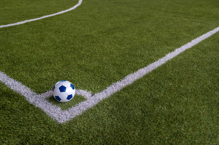 Soccer football in corner of artificial grass field with copy spaces. Corner kick is for restarting play when ball goes out over goal line without score and last touched by defender. Stock Photo