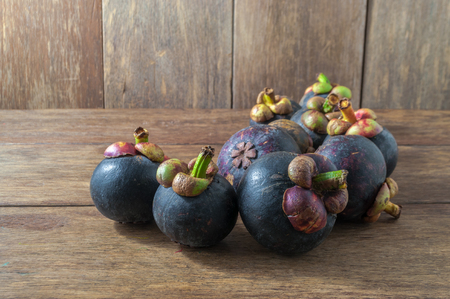 Closeup of several purple mangosteens various angles on wooden table. Mangosteen is native plant to Sunda Islands and the Moluccas of Indonesia. Grows in tropical areas. Designated as Queen Of Fruits.