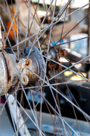 Closeup selected focus of rusted old bicycle wheel parts waiting for repair in local bicycle shop. Stock Photo