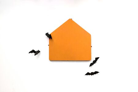 Empty orange house shape plate on white wall with four black bats around for halloween theme text or pictures. isolated on white background. plenty of copy space.
