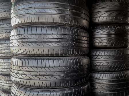 shiny black recapped car tires stack. they are inspected and repair and good to be used in lower cost than new tires. Stock Photo
