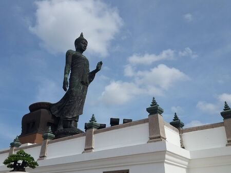 Large walking buddha statue in Thailand shot from the side against blue sky with some clouds.