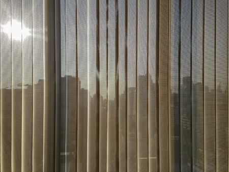 beige, brown color semi transparent vertical blinds with blurred afternoon sun and business district buildings seen trhough in the background. the vertical blinds help prevent heat and ultraviolet.