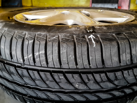 white arrow mark the leaking point on car tire. sometimes the leaking can not be seen with bare eyes, tire must be checked by putting under water and see air bubble and mark the position for repair.