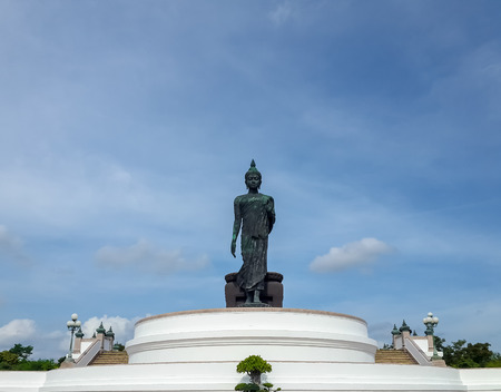 Large walking buddha statue in Thailand shot from the front against blue sky with some clouds. Stock Photo