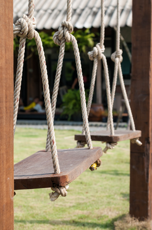 Selected focus wooden swing hung by ropes in green lawn playground under afternoon sunlight.