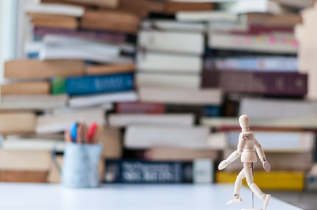 Wood manikin walking toward mountain of books blurred in the background with a blurred pencil cup. Education concept. Stock Photo