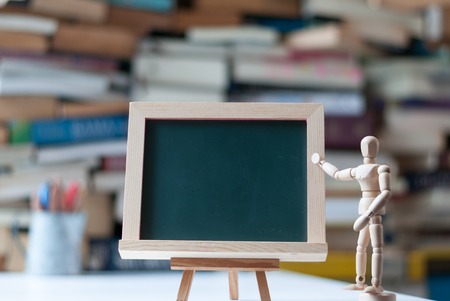 Empty green board on tripod with wood manikin pointing at it with blurred book pile and pencil cup as background. Education concept. Stock Photo