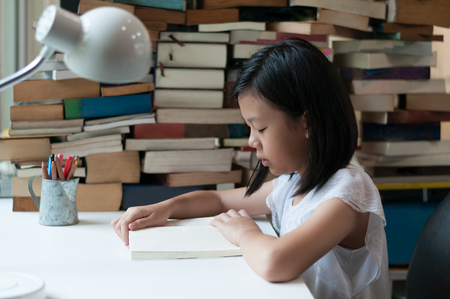 Young Asian teenage girl reading a book with blurred book pile and blurred pencil cup in background. Education theme