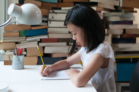 Young Asian teenage girl writinng in note book with blurred book pile and pencil cup in background. Education theme