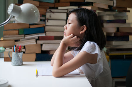 Young Asian teenage girl with homework book in fron but look away feeling boring. Education theme