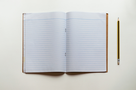 Top view of blank school workbook with blue lines and a pencil with yellow and black stripes on pale table top
