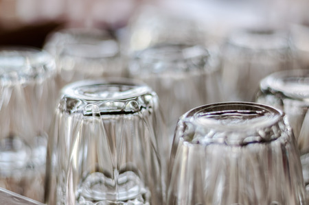 Selected focus close up on bottom of empty transparent drinking glasses placed upside down in group on a table.