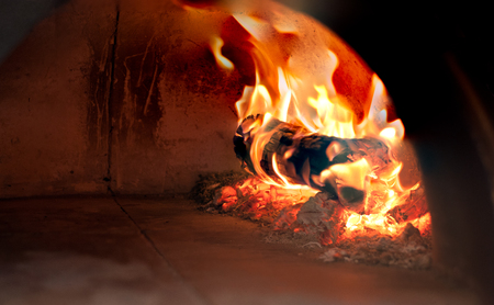 closeup burning wood and charcoal inside italian traditional pizza oven through the open end