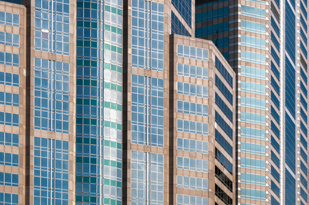 closeup to detail of dense buildings in business district area showing multiple color of glass windows and building structure.