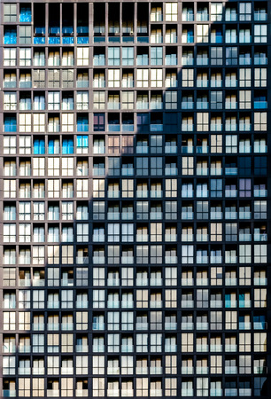 closeup to detail of highrise residential condominium building presenting glass windows repatitive pattern with diagonal shadow of adjacent building