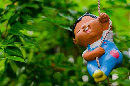 Happy Clay doll playing swing  Stock Photo