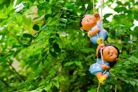 Double Happy Clay doll playing swing
