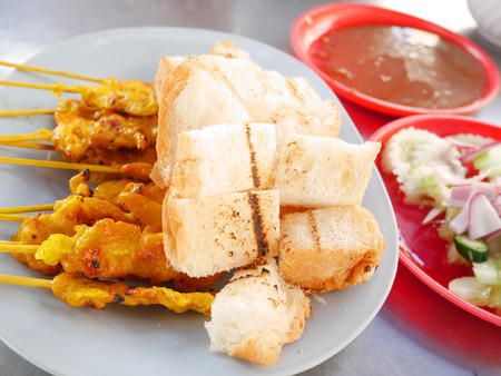 satay sauce: Pork Satay and toast served with peanut sauce and vegetables Stock Photo
