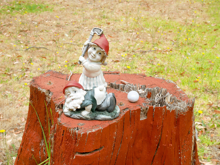 Gnomes playing golf on a stump at golf course