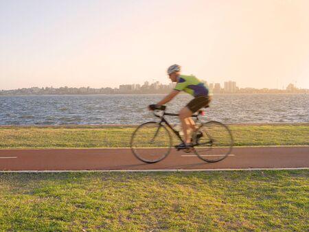 biker man: Blurred young man cycling on bike lane along the river in evening light Stock Photo