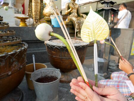make belief: A man holding joss stick and lotus for paying respect to the Buddha Stock Photo