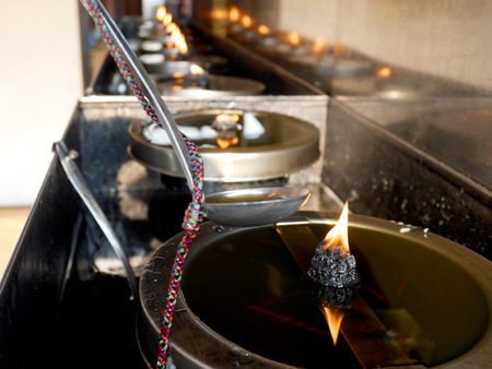 make belief: A buddhist filling the oil lamp merit at temple Stock Photo