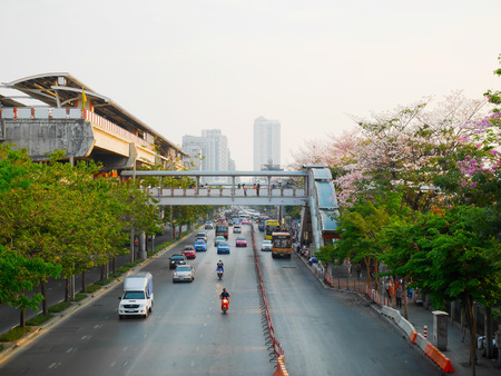 Bangkok, Thailand - 17 april: Sky station, het verkeer en tabebuia rosea bomen langs de weg in Bangkok op de laatste dag van lang weekend in de avond op 17 april 2016