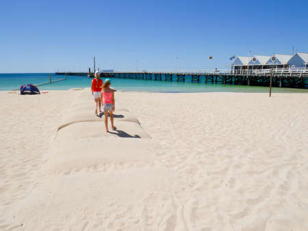 busselton: Busselton, Western Australia - January 13: Girls with bright clothes walk on the beach in Busselton on January 13, 2016 Editorial