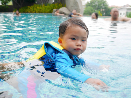 trying: Little boy trying to swim with life jacket