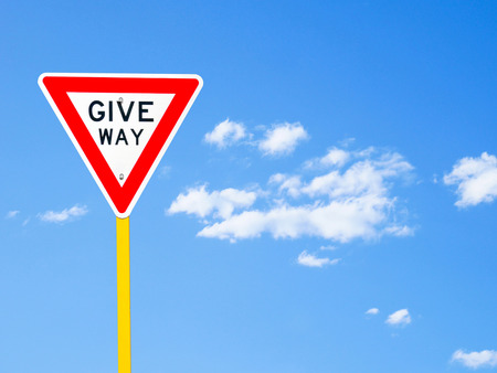 give way: Give way sign on blue sky background (with clipping path)