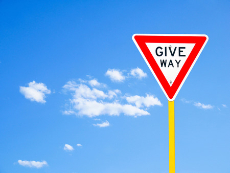 give the way: Give way sign on blue sky background