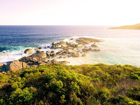 western australia: High angle view of wave crashing against rocks and sunset at Lowlands beach, Western Australia