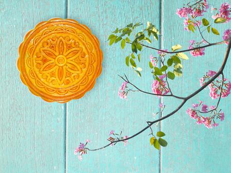 Durian mooncake voor medio-de herfstfestival en bloemendecoratie op blauwe houten achtergrond