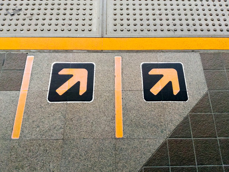 visually: Yellow arrows sign and tactile paving for the visually impaired at train station in Bangkok Stock Photo